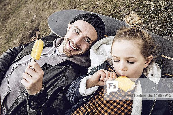 Vater und Tochter ruhen sich auf dem Skateboard aus und essen Eis