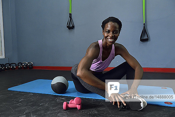 Portrait of happy woman sitting on a mat in a gym