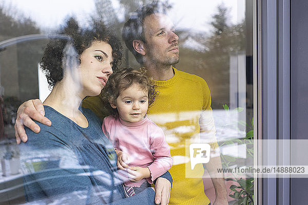 Glückliche Familie schaut aus dem Fenster  Mutter trägt Tochter