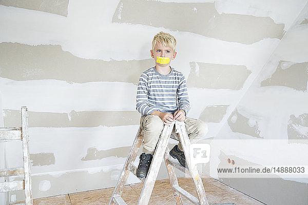 Wütender Junge mit zugeklebtem Mund sitzt auf einer Leiter auf dem Dachboden  die renoviert werden soll