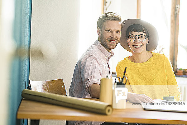 Portrait of happy couple at wooden table in their home office