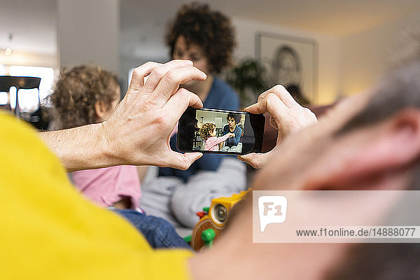 Mother and daughter playing in living room  fater taking smartphone pictures