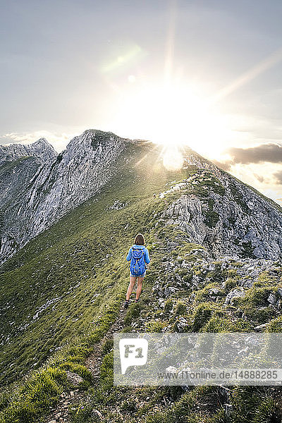 Austria  Tyrol  woman on a hiking trip in the mountains at sunset