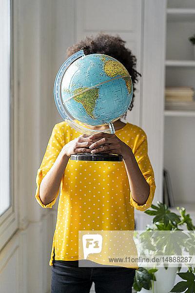 Woman holding globe  hiding face