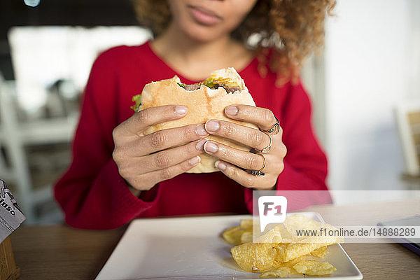 Close-up of woman's hands holding a hamburger