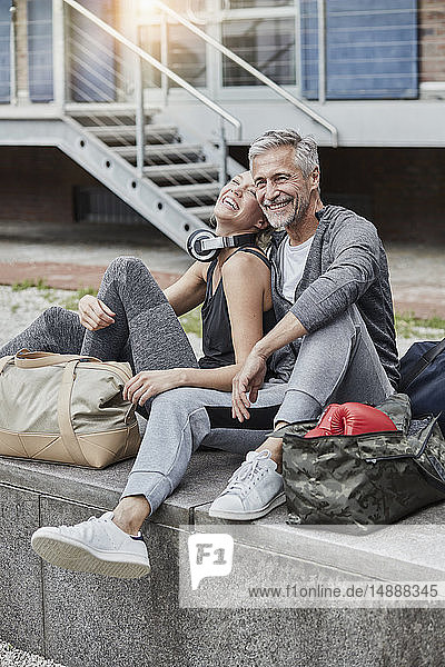 Laughing mature man and young woman with sports bag sitting in front of gym