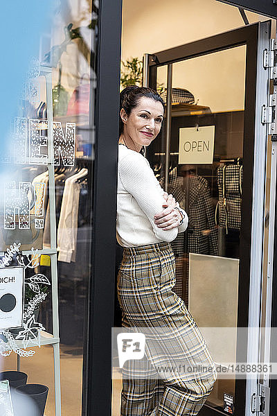 Shop owner standing in door of fashion store  with arms crossed