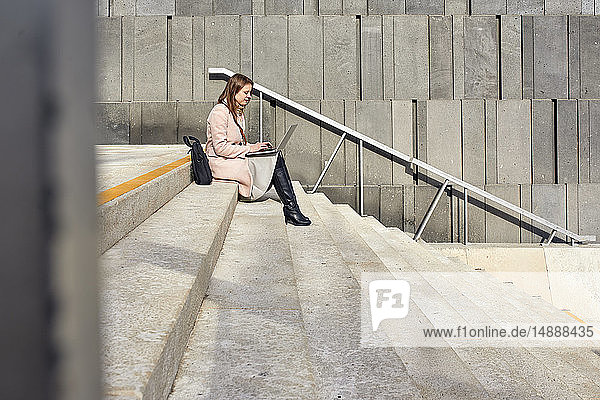 Austria  Vienna  young woman sitting on stairs at MuseumsQuartier using laptop