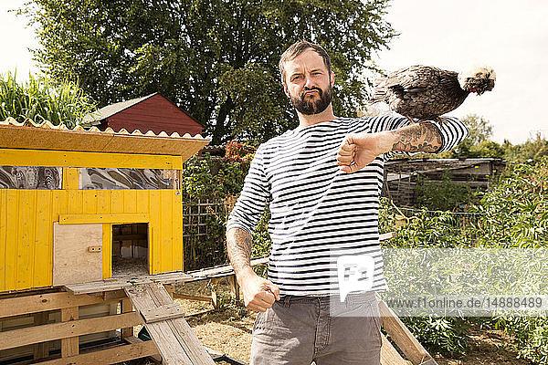 Porträt eines Mannes mit polnischem Huhn im Hühnerstall im Garten