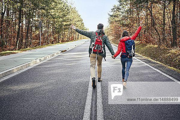 Glückliches Paar geht mitten auf einer leeren Straße im Wald