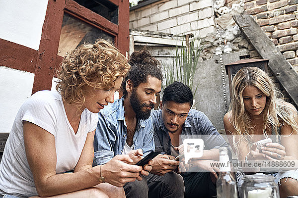 Friends sitting in a backyards  using smartphones