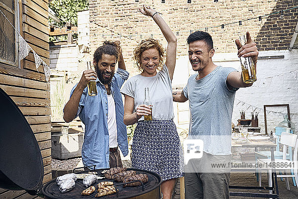 Friends having a barbecue n the backyard  preparing meat on a grill