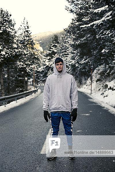 Junger Mann steht auf einer verschneiten Straße mit Bäumen im Hintergrund