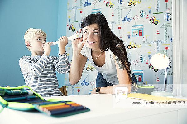 Mutter und Sohn haben Spaß am Schreibtisch im Kinderzimmer