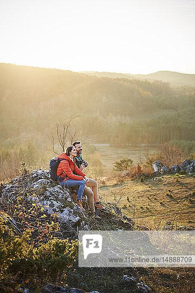 Paar auf einer Wanderung in den Bergen bei einer Pause auf einem Fels sitzend
