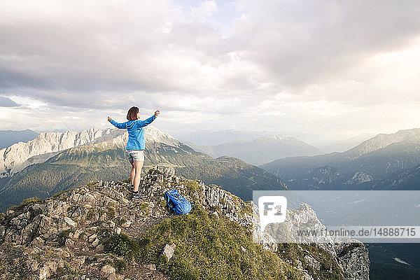 Österreich  Tirol  Frau auf einer Wanderung in den Bergen jubelt auf dem Gipfel