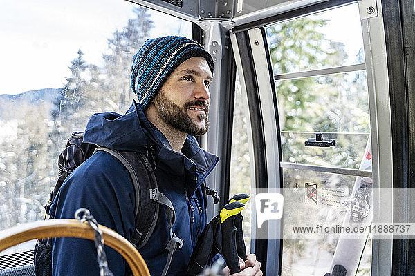 Deutschland  Bayern  Brauneck  lächelnder Mann im Winter in der Gondelbahn