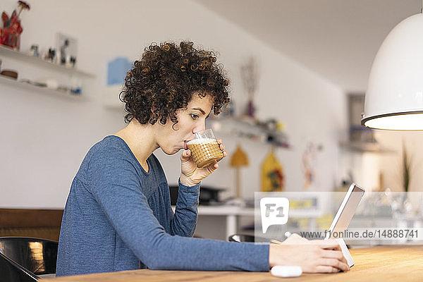 Junge Frau sitzt am Tisch,  benutzt digitales Tablett,  trinkt Kaffee