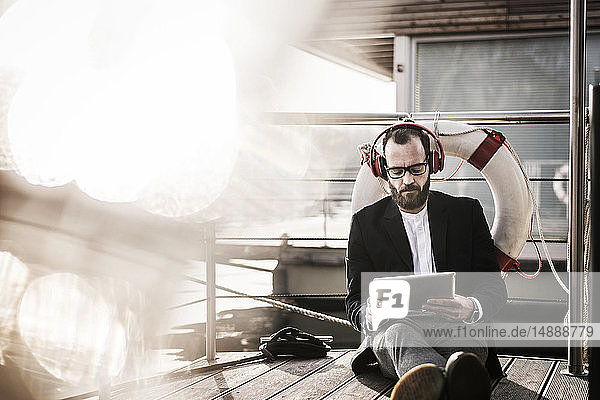 Angesagter Geschäftsmann  der auf einem Hausboot arbeitet  mit Kopfhörer und digitalem Tablet