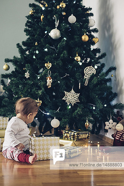 Auf dem Boden sitzendes Mädchen spielt mit Weihnachtsgeschenken