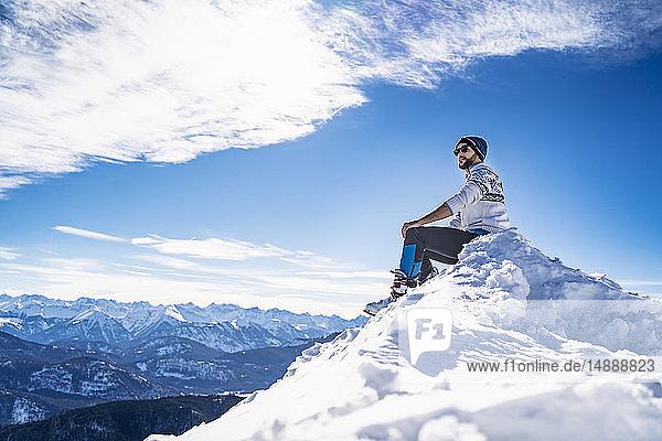 Deutschland  Bayern  Brauneck  Mann im Winter auf Berggipfel sitzend