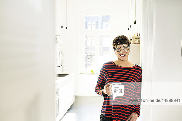 Confident short-haired woman with coffee mug leaning against door case