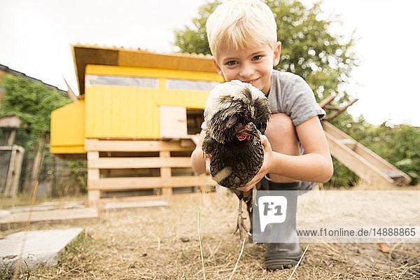 Junge hält polnisches Huhn im Hühnerstall im Garten