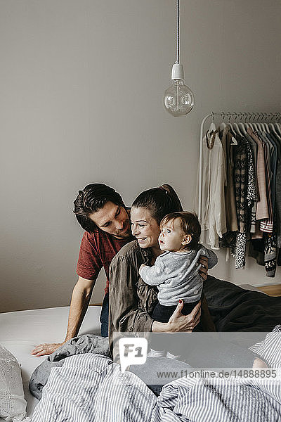 Glückliche Familie mit einem kleinen Mädchen  das zu Hause auf dem Bett sitzt