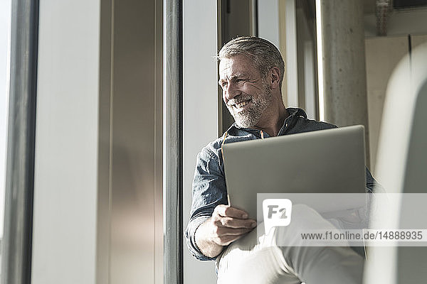Lächelnder  lässiger  reifer Geschäftsmann mit Laptop  der aus dem Fenster schaut