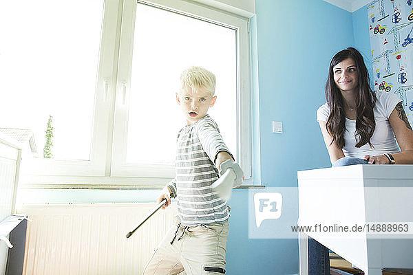 Mutter beobachtet Sohn beim Spielen im Kinderzimmer