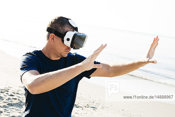 Man wearing VR glasses on the beach