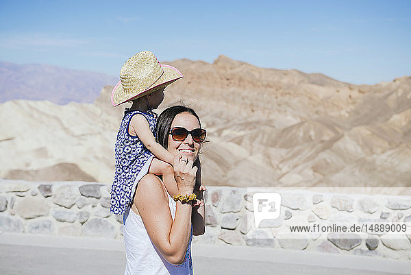 USA  California  Death Valley National Park  Twenty Mule Team Canyon  smiling mother carrying baby girl