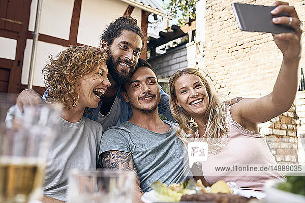 Friends having fun at a barbecue party  taking pictures with their smartphones