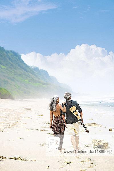 Rückenansicht eines älteren Hippie-Paares mit Gitarre  das Seite an Seite am Strand spazieren geht