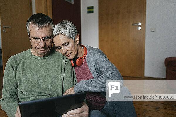 Älteres Ehepaar sitzt zu Hause auf dem Boden und schaut auf die Tablette