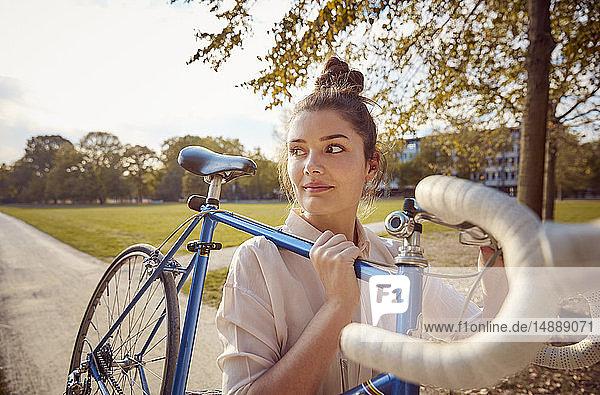 Junge Frau mit Fahrrad in einem Park