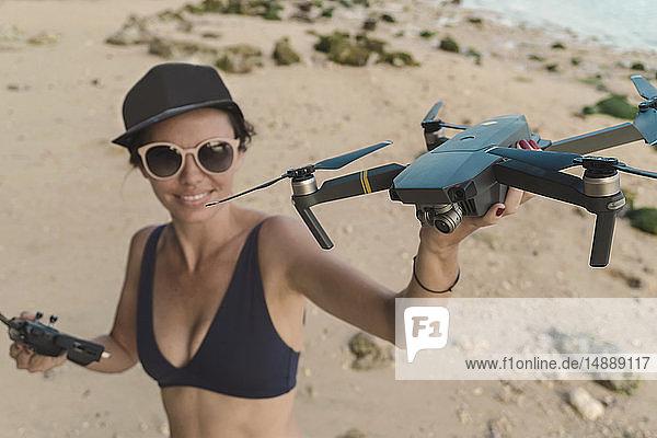 Indonesia  Bali  Nusa Dua  woman holding drone at the beach