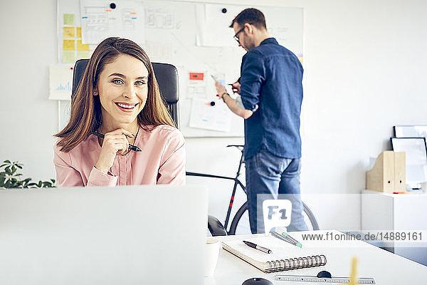 Porträt einer lächelnden Frau  die am Schreibtisch im Büro arbeitet  mit einem Kollegen im Hintergrund