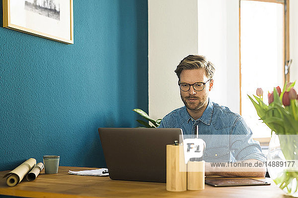 Casual businessman in home office working at his laptop