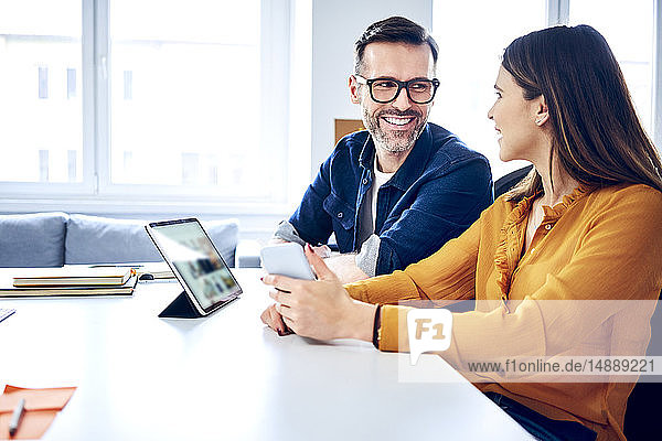 Two colleagues working together on tablet and smartphone in office