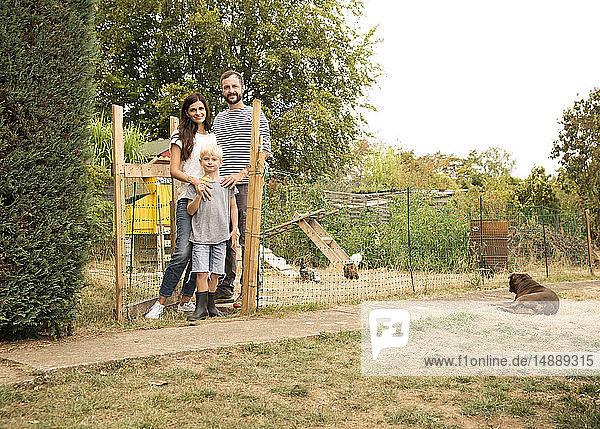 Porträt einer selbstbewussten Familie  die im Hühnerstall im Garten steht