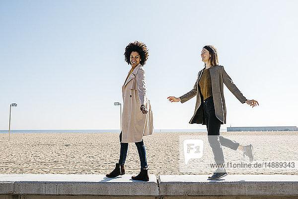 Zwei glückliche Freunde spazieren auf der Promenade und genießen ihre Freizeit