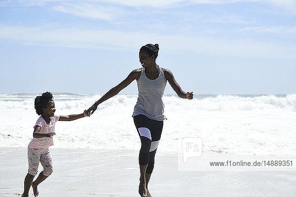 Glückliche Mutter und Tochter amüsieren sich am Strand