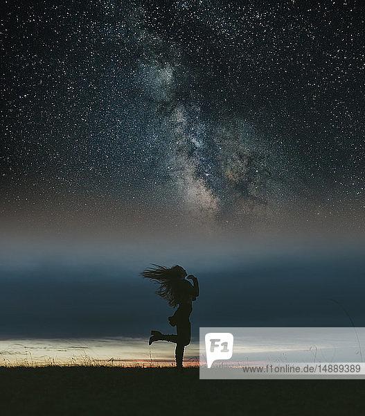 Silhouette einer Frau  die auf einer Wiese unter dem Sternenhimmel tanzt