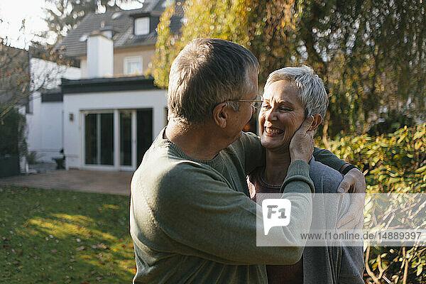 Glückliches  anhängliches Seniorenpaar umarmt sich im Garten