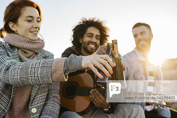 Drei glückliche Freunde bei Sonnenuntergang mit Gitarre auf Bierflaschen anstoßen