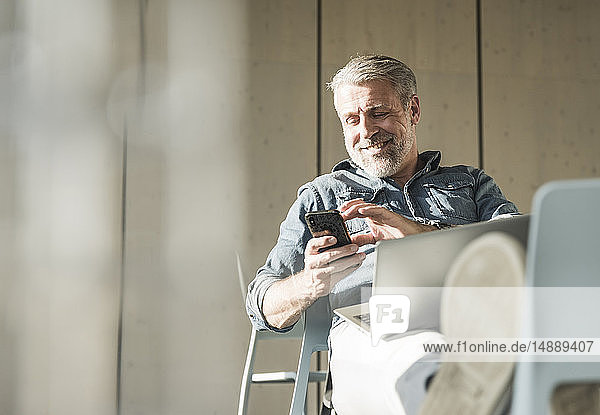 Smiling casual mature businessman with laptop and cell phone