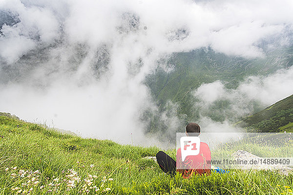 Man taking a break from his hike sitting in the grass in the Carpathian Mountains  Romania