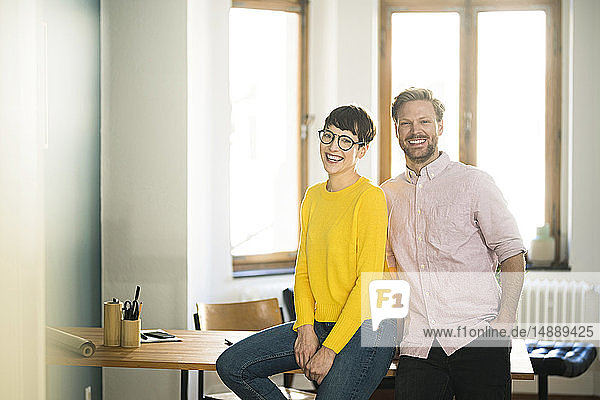 Portrait of happy couple at table in stylish apartment