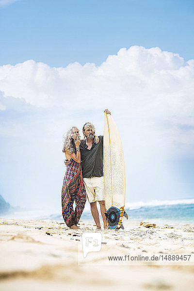 Senior hippie couple standing with surfboard on the beach